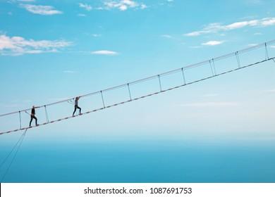 Young woman crossing the chasm on the rope bridge. Ai-Petri, Crimea