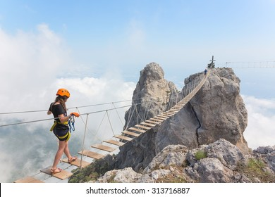 Young woman crossing the chasm on the rope bridge