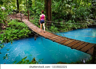 Young woman crossing a hanging bridge in the Jungle of Costa Rica. The river (rio celeste in tenorio national park close to Bijagua) has an emerald green color, caused by volcanic minerals