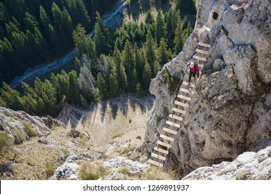 Young woman crossing the suspended footbridge on Wild Ferenc via ferrata route in Romania. Sunny day of autumn in the mountains. Extreme adventure.