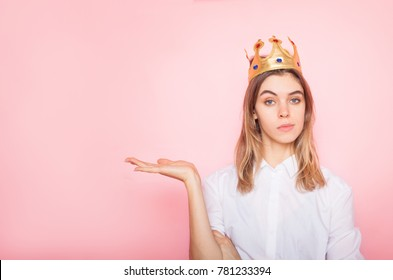 Young woman in crown holding something imaginary on palm of her