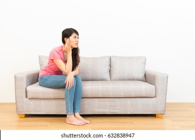 young woman crushed ear painful position sitting on couch looked at white background with wood floor at home in living room.