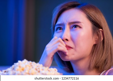 Young woman cry while watching a tragedy movie at night