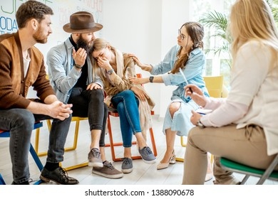 Young woman crying during the psychological therapy with group of people supporting her in the office