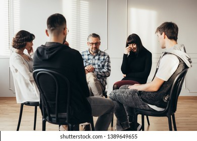 Young woman crying during widow and widowers support group meeting