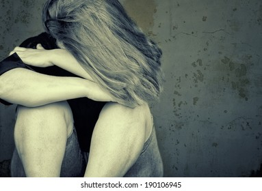 Young woman crying sitting on the floor with a grunge background