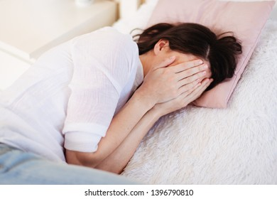Young woman crying while lying in bed. Cover her face with her hands