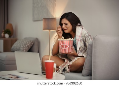Young woman crying while watching movie at home