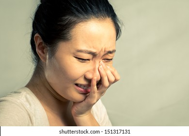Young woman crying and wiping tears, with fashion tone