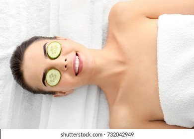 Young woman with cucumber slices in spa salon