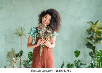 Young woman cultivating home plants.Small business.Sensual mixed race female florist with flowers in hands against background of indoor plants. Life lover, zero waste, inspiration, summer mood concept - Shutterstock ID 1650941752