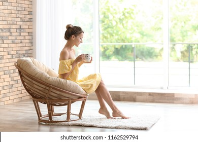 Young woman with cup of aromatic coffee sitting in papasan chair near window at home