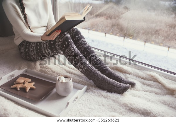 Young woman with cup of coffee and gingerbread is reading a book sitting home relaxing by the window. Snow winter home chill out concept