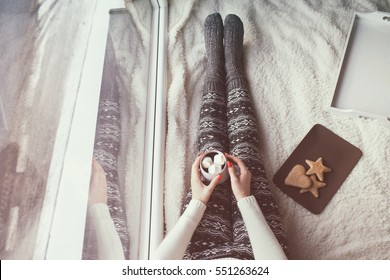 Young woman with cup of coffee with marshmallows and gingerbread sitting home relaxing by the window. Snow winter home chill out concept