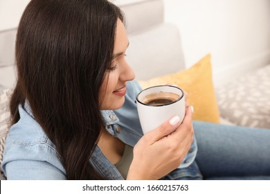 Young woman with cup of drink relaxing on couch at home