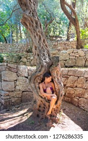 Young woman curled up in an old olive tree trunk, surrounded with rock wall, hugging the knees. Concept olive oil skin care, pearl in the shell, core, nature lover, one with nature, longevity