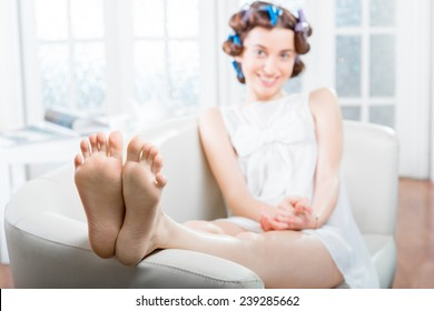 Young woman with curlers in her hair relaxing in the couch at white domestic interior