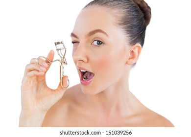 Young woman curling her eyelashes on white background