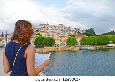 Young woman with curly brown hair in dark blue dress reading the tourist map on the Santa Clara Bridge in portuguese Coimbra. Beautiful old town along the Mondego River in the background. Sep 4th 2018