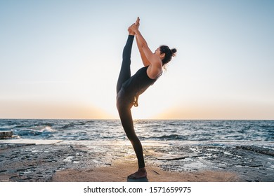 Young woman with curly hair in black costume practicing yoga at sunrise light, minimalist scene. Doing asana. Healthy lifestyle concept.