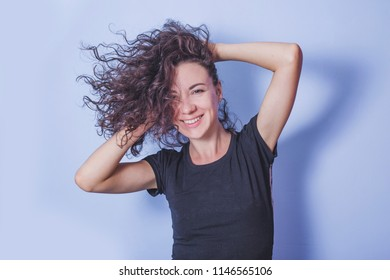 Young woman with curly hair on blue background