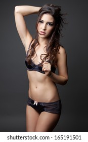 Young woman with curly hair posing in lingerie