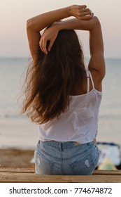 young woman with curly hair sittin on the morning beach