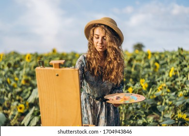 A young woman with curly hair and wearing a hat is painting in nature. A woman stands in a sunflower field on a beautiful day.