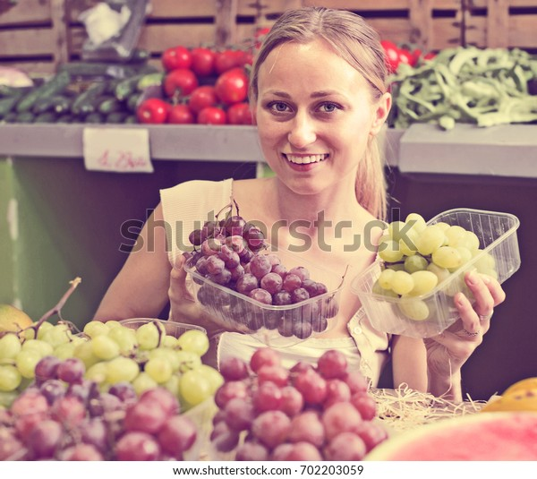 young woman customer choosing grapes on market