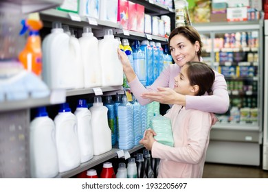 Young woman customer with girl looking for cleaners for home in a supermarket. Focus on woman