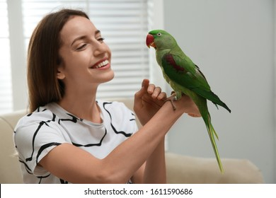 Young woman with cute Alexandrine parakeet indoors
