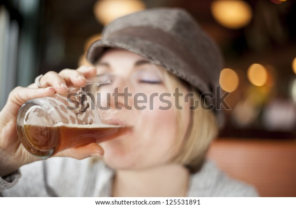Young woman in cute brown hat drinking a beer.