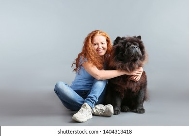 Young woman with cute Chow-Chow dog on grey background