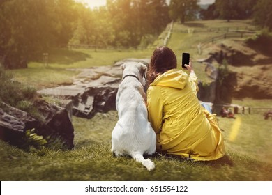 young woman and cute labrador retriever dog puppy are sitting side by side on a hill and make a selfie