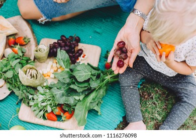 Young woman and cute little kids relaxing at summer picnic with healthy food