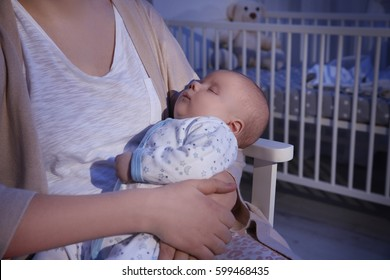 Young woman with cute sleeping baby in evening at home, closeup