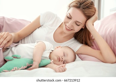 Young woman with cute sleeping baby lying on bed at home