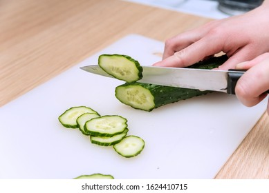 Young woman cuts cucumber in the kitchen. Close up