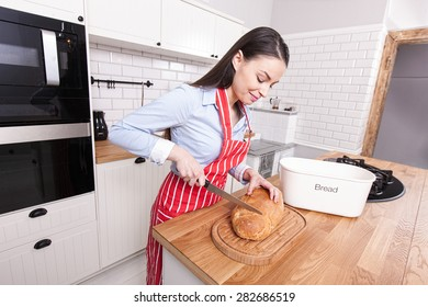 Young woman cutting bread in kitchen.