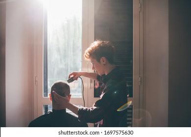 Junge Frau, die zu Hause die Haare eines Mannes schneidet - Haarpflege, Haarschnitt, Selbstisolierungskonzept