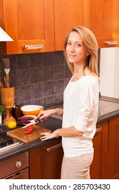 Young Woman Cutting Tomato in the Kitchen