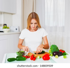 Young woman cutting vegetables at the kitchen