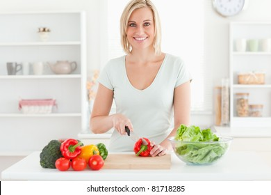 Young woman cutting vegetables smiles into camera in kitchen
