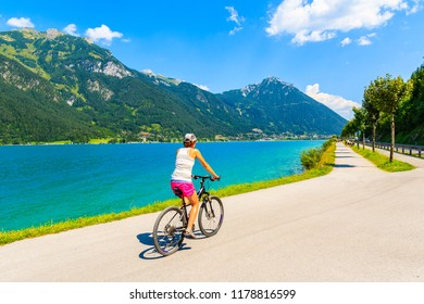 Young woman cycling along Achensee lake in Pertisau town, Tirol, Austria