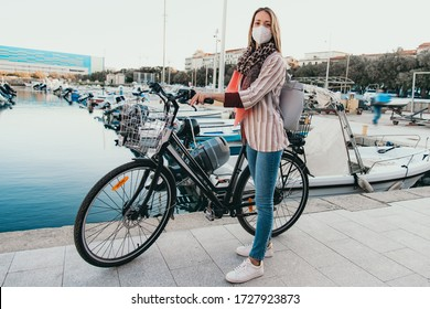 Young woman cycling along the jetty, wearing medical mask. Global pandemic Coronavirus or Covid-19.