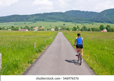 Young woman cycling in the hills, Poland
