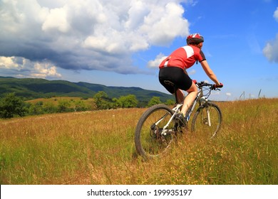 Young woman cycling on countryside road during summer
