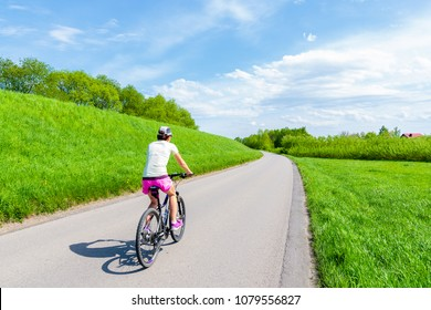 Young woman cycling on rural road along Vistula river near Krakow city during spring season, Poland