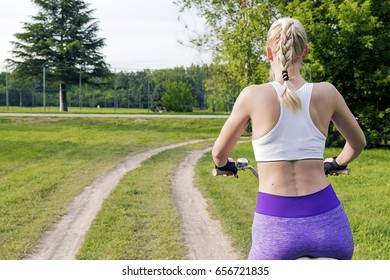 Young Woman Cycling. Young pretty woman in sport suite riding a bicycle on the forest road. Healthy lifestyle concept. Sports girl with bike. Healthy lifestyle and recreation leisure activity.