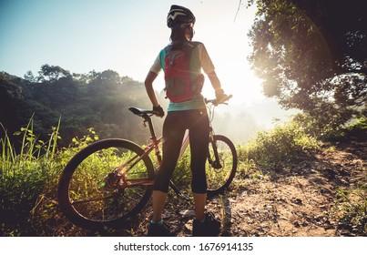 Junge Radlerinnen genießen den wunderschönen Sonnenaufgang auf dem Waldweg